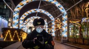 Ochranka v téměř prázdném obchodním centru v Pekingu sleduje telefon; 27. února 2020