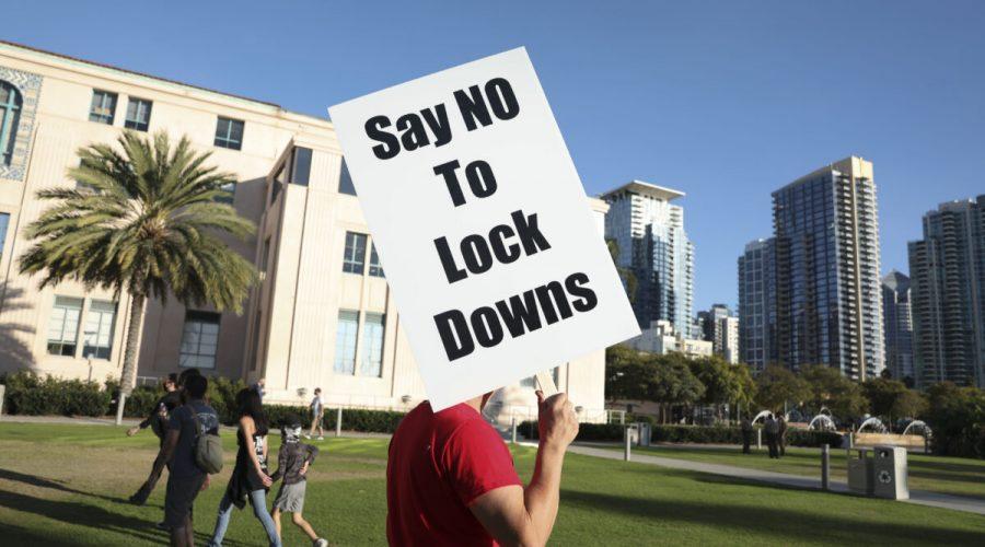 Muž drží ceduli s nápisem proti lockdonům během shromáždění u budovy okresní správy v kalifornském San Diegu, 16. listopadu 2020.